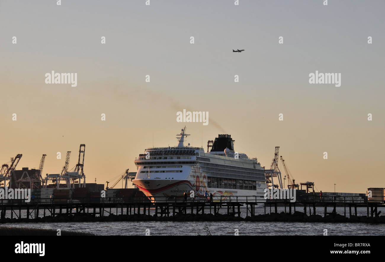 Airliner above 'Norwegian Sun' cruise ship, sailing from the Puerto Nuevo Docks towards a pier at Costanera - Stock Image