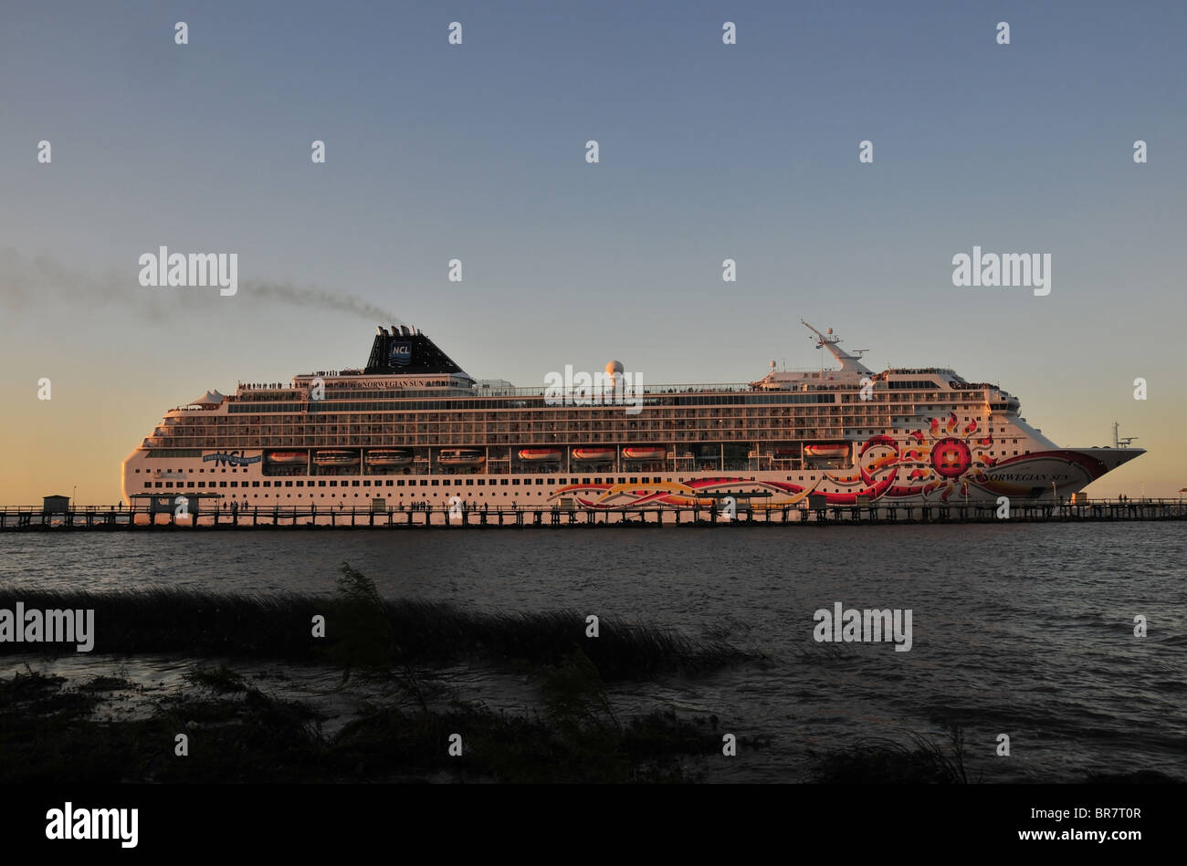 Side profile view of cruise ship 'Norwegian Sun', moving past a pier at the Ecologica Costanera Sur Nature - Stock Image