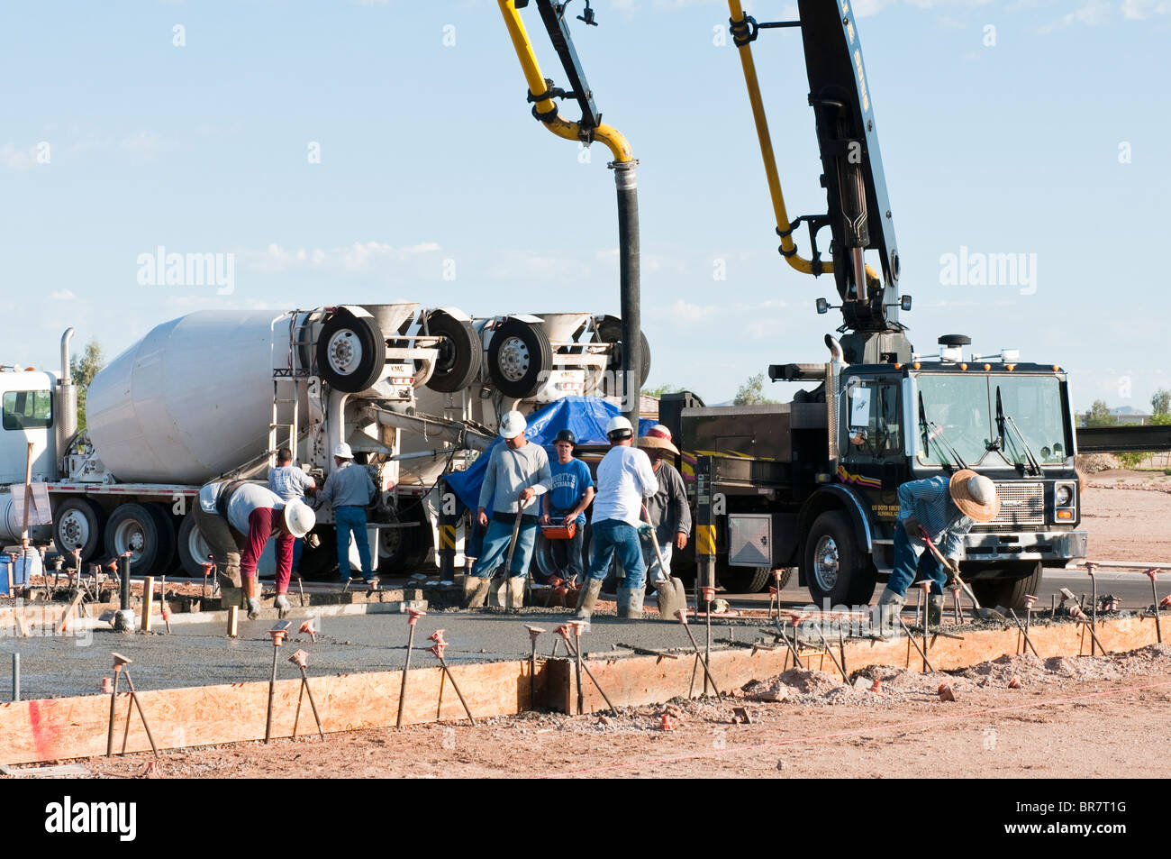 A crew of workers pour a concrete slab for a new house under construction in Arizona. - Stock Image