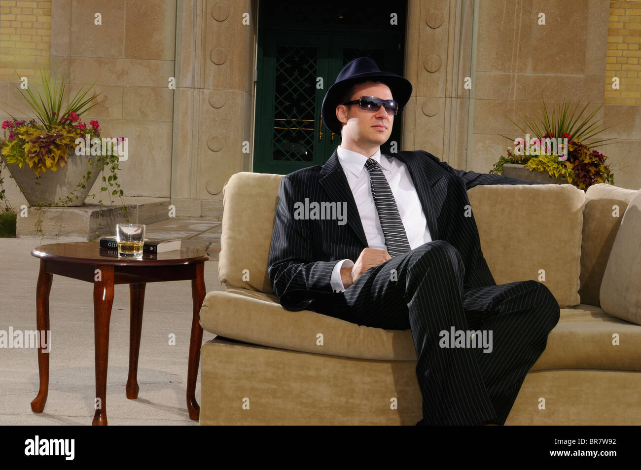 Gangster in hat and suit relaxing on a couch at a mansion with outdoor terrace RC Harris water treatment plant Toronto - Stock Image