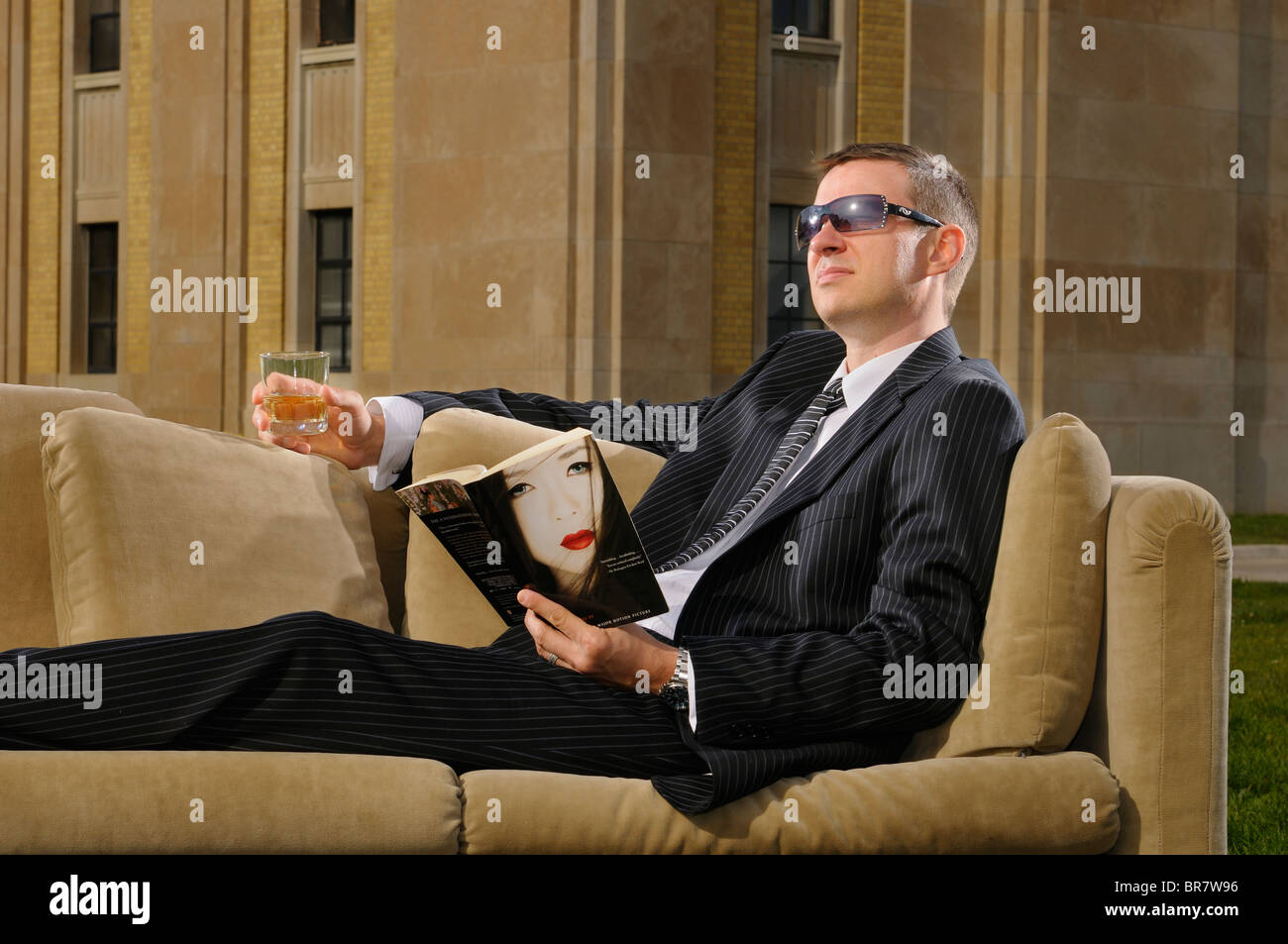 Wealthy young man in suit lying on a couch drinking and reading pulp fiction at an Art Deco mansion RC Harris water - Stock Image