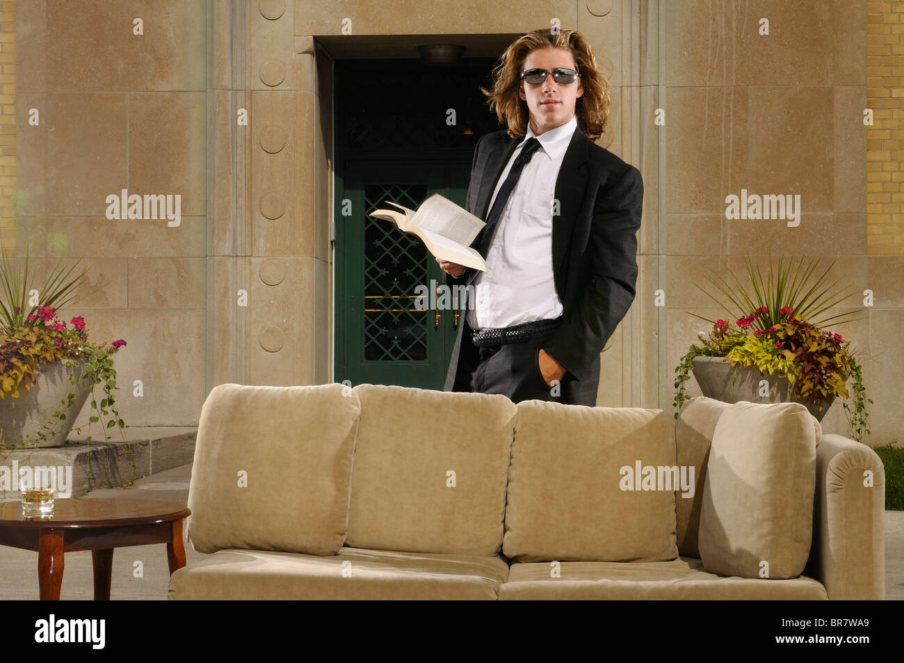 Wealthy young man with long blond hair in suit behind a couch with a paperback book on an outdoor terrace at a mansion - Stock Image