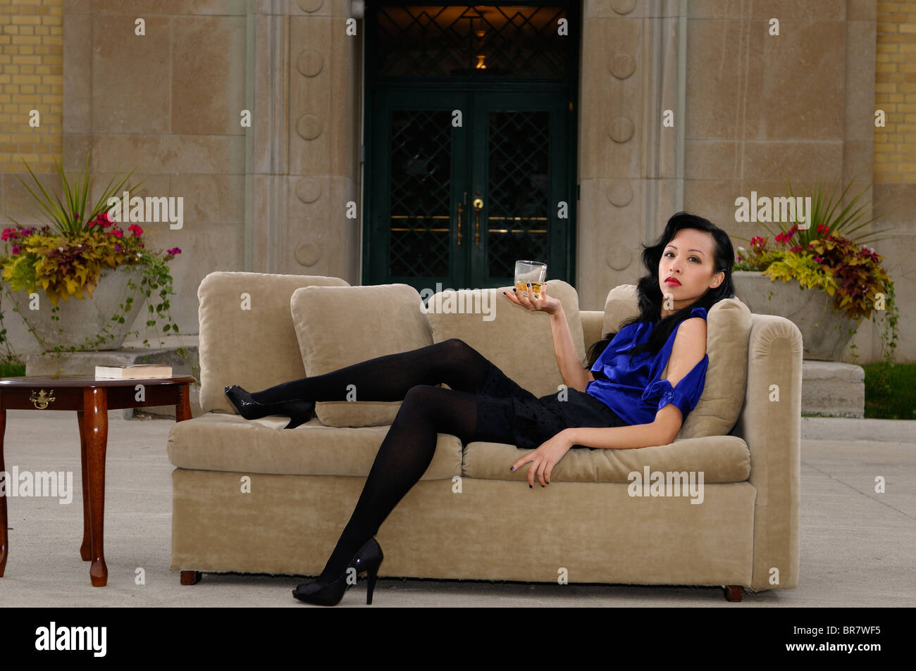 Attractive Asian woman reclining on a couch at an outdoor patio at an Art Deco mansion Harris Water Treatment Plant - Stock Image
