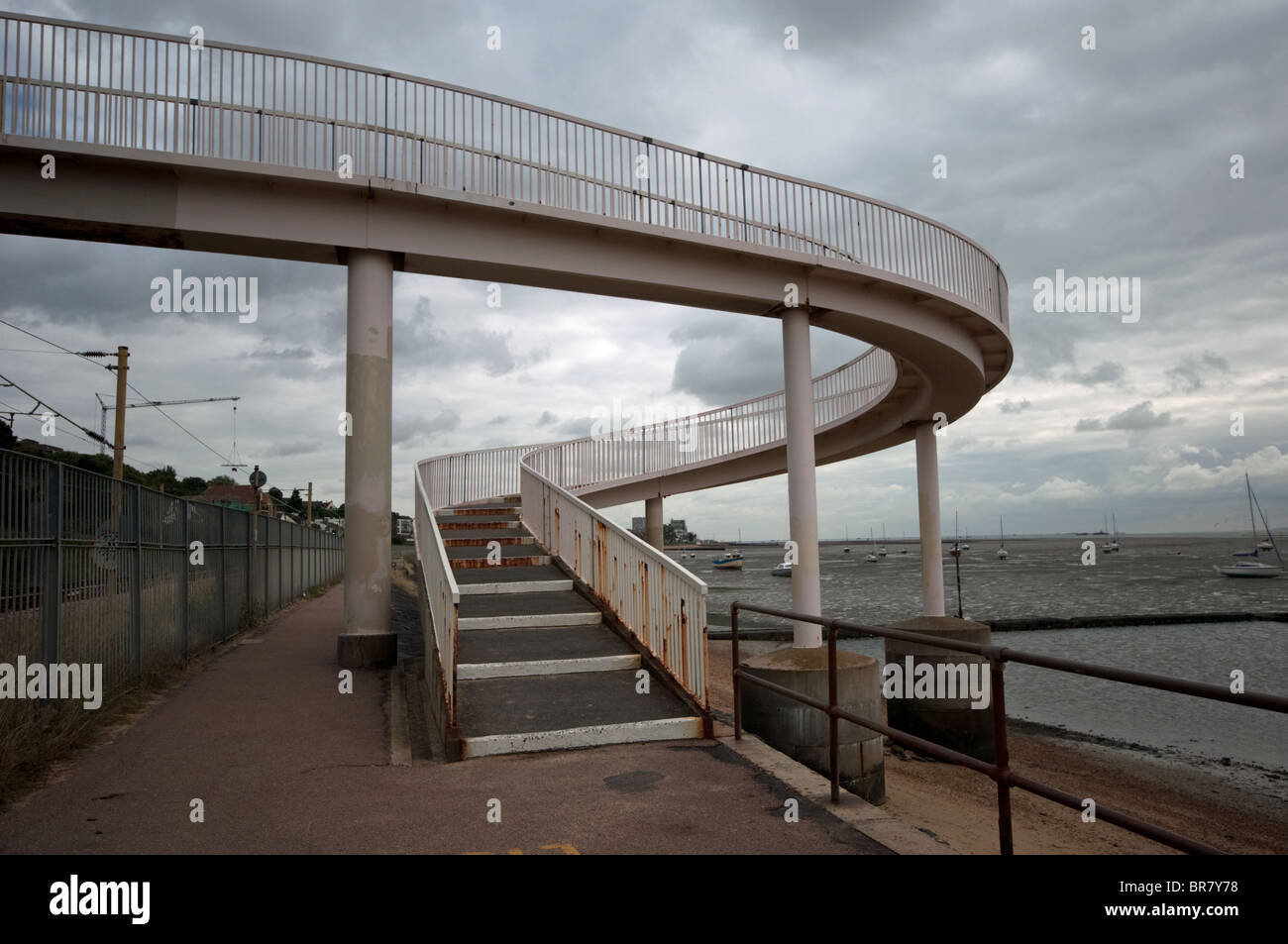 Curved ramp to distressed pedestrian bridge over railway track by the coast Stock Photo
