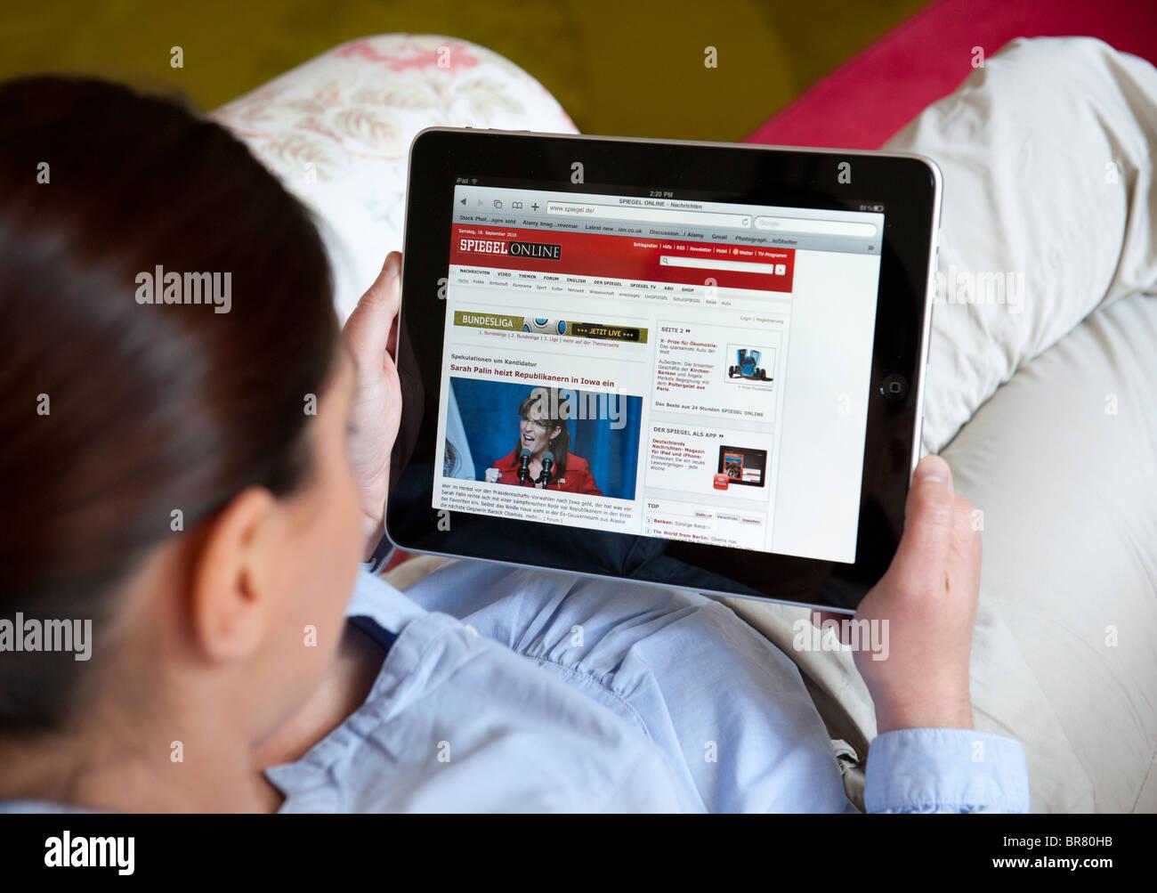 Woman using iPad tablet computer to read Der Spiegel magazine online - Stock Image