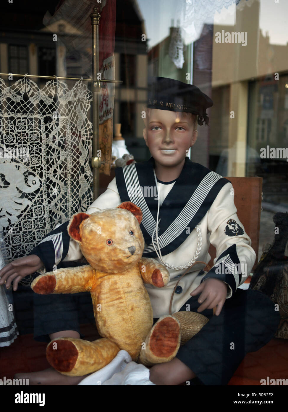 Sailor doll and teddy bear in a shopwindow in Antwerp, Belgium - Stock Image