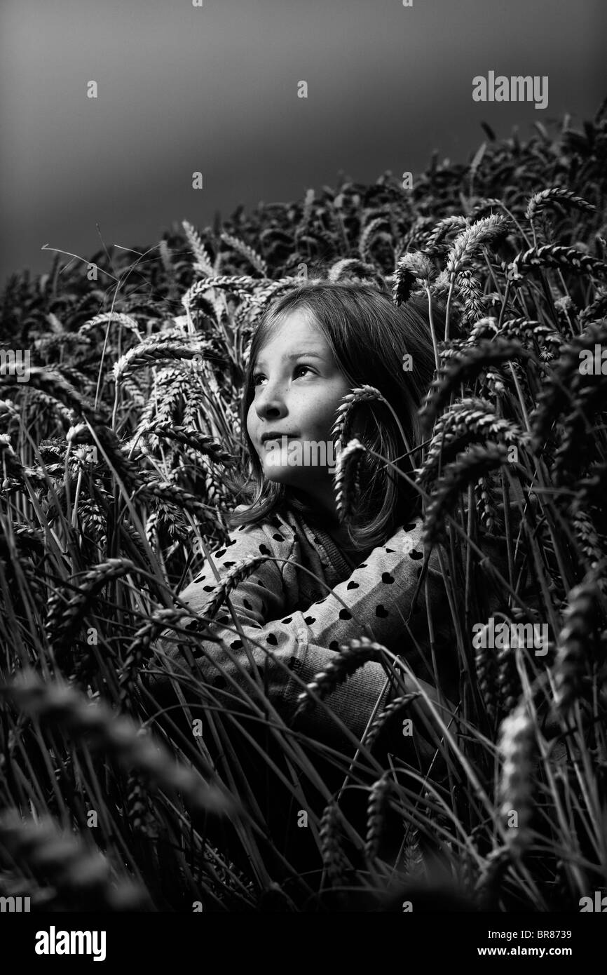 Black and White image of a girl sat in a wheat field. - Stock Image