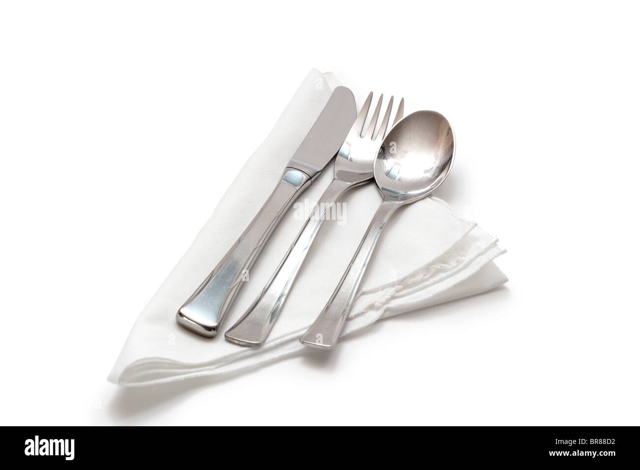 Knife, fork, and spoon on a white cotton napkin - Stock Image