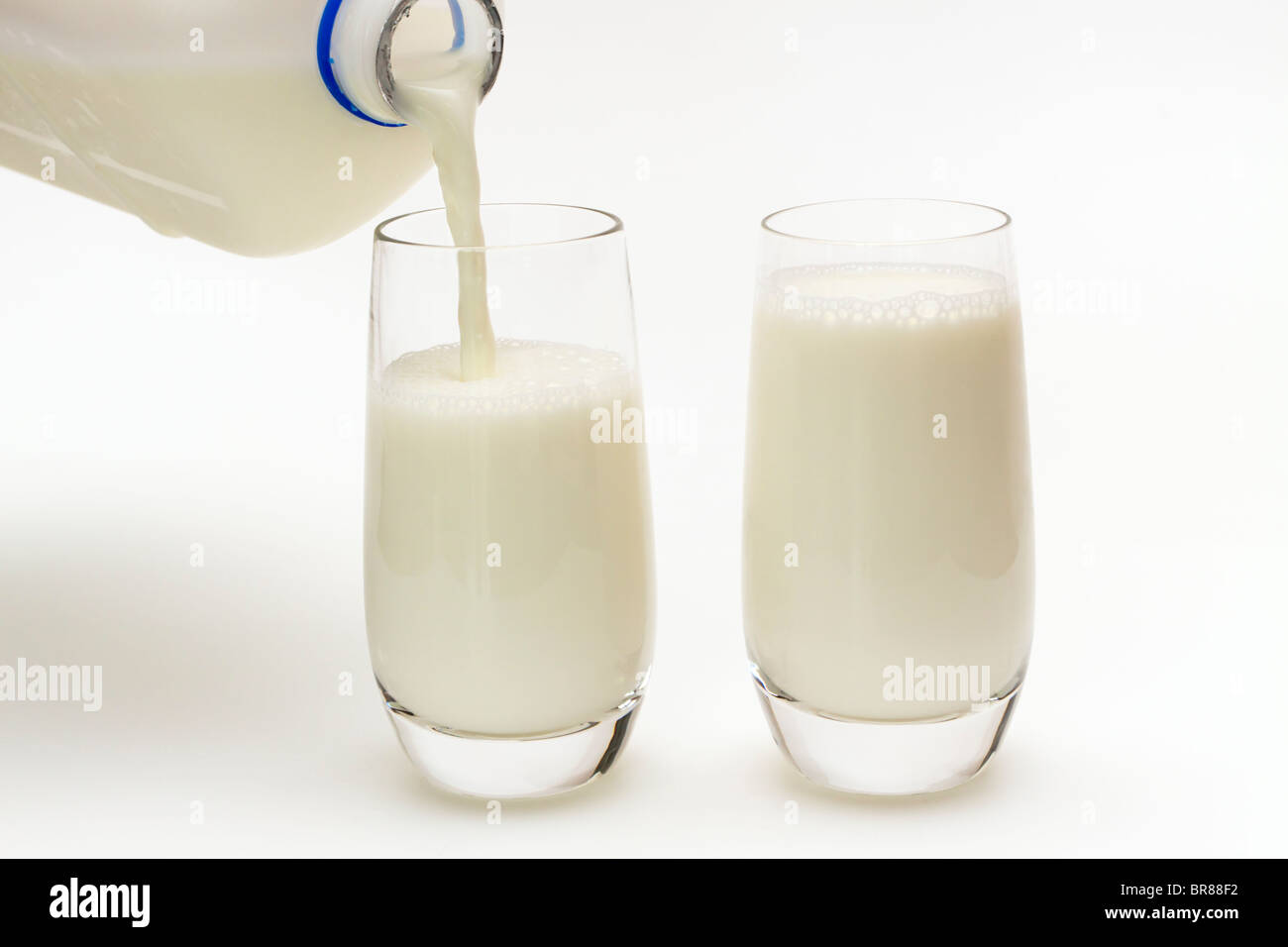 Pouring two glasses of milk Stock Photo