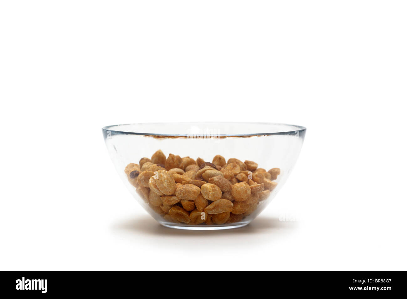 Roasted shelled peanuts in a glass dish.  An unhealthy snack. - Stock Image