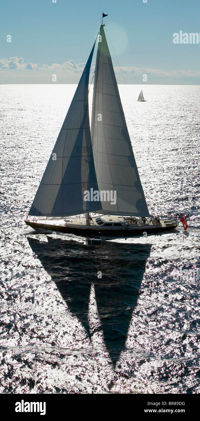 116ft Ted Hood designed superyacht 'Whisper' sails past the distant 'Black Tie'. - Stock Image