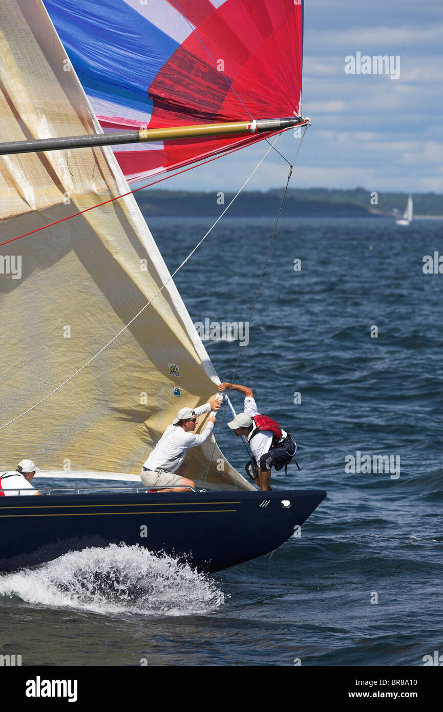 The crew on 'Freedom' take down the head sail after the spinnaker is flying while racing in the 12 Metre - Stock Image
