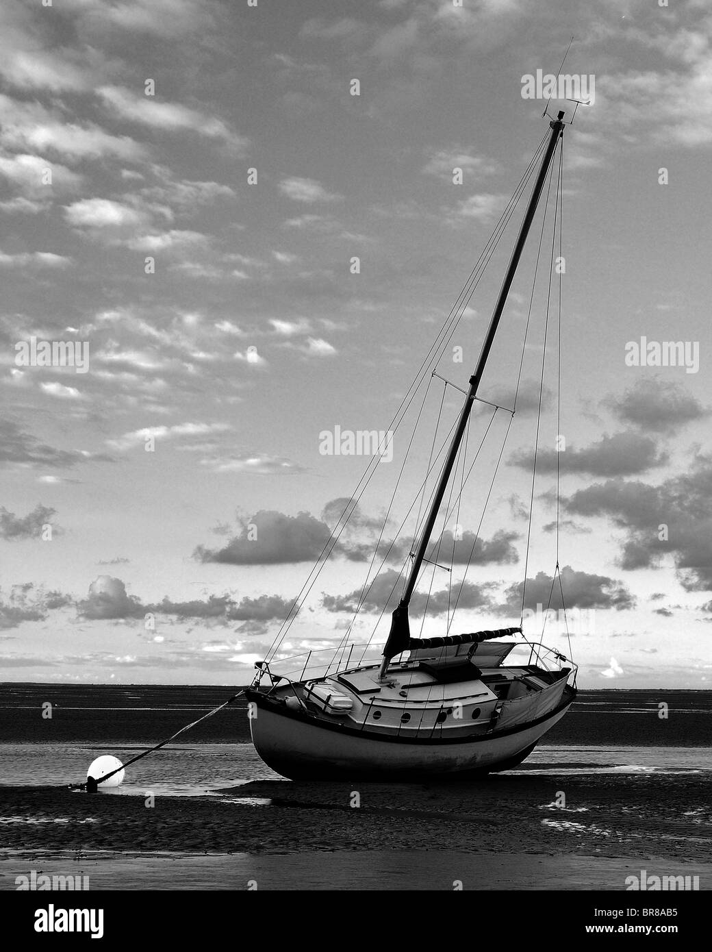 boat sunset low tide sand clouds soft lighting - Stock Image