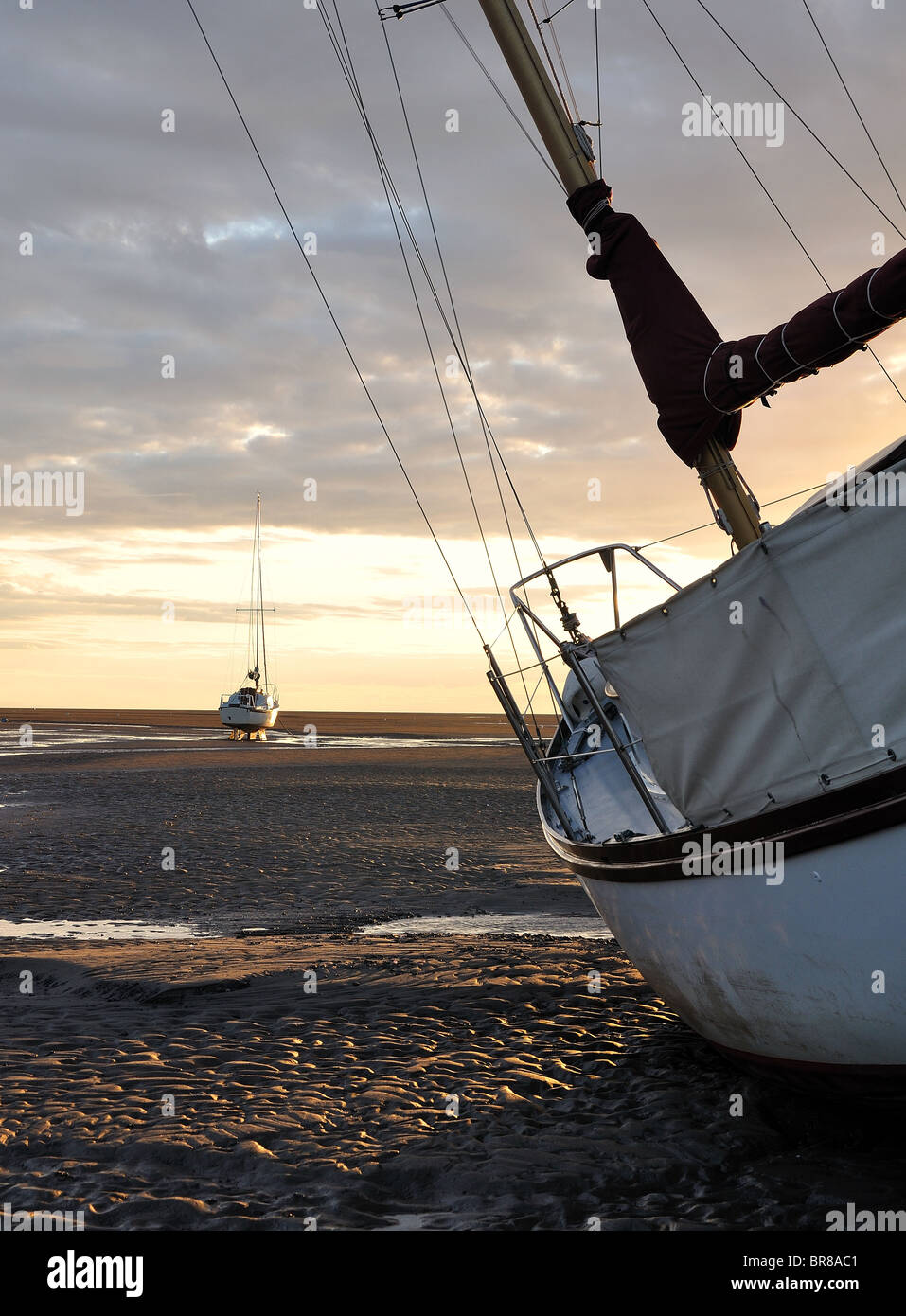 Boat lay on low tide sands in a sunset - Stock Image