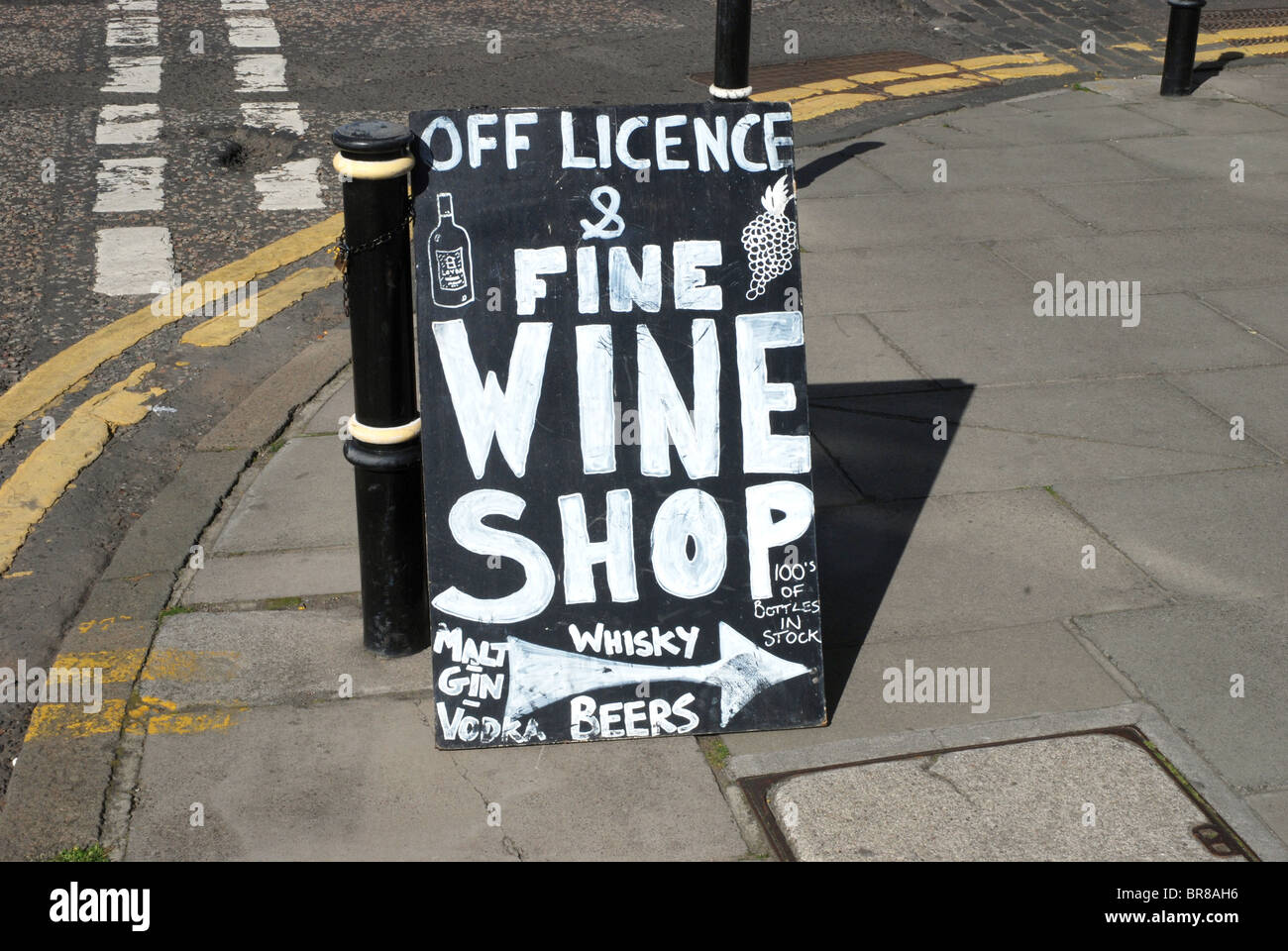A sign pointing to an off licence in Edinburgh's New Town. - Stock Image