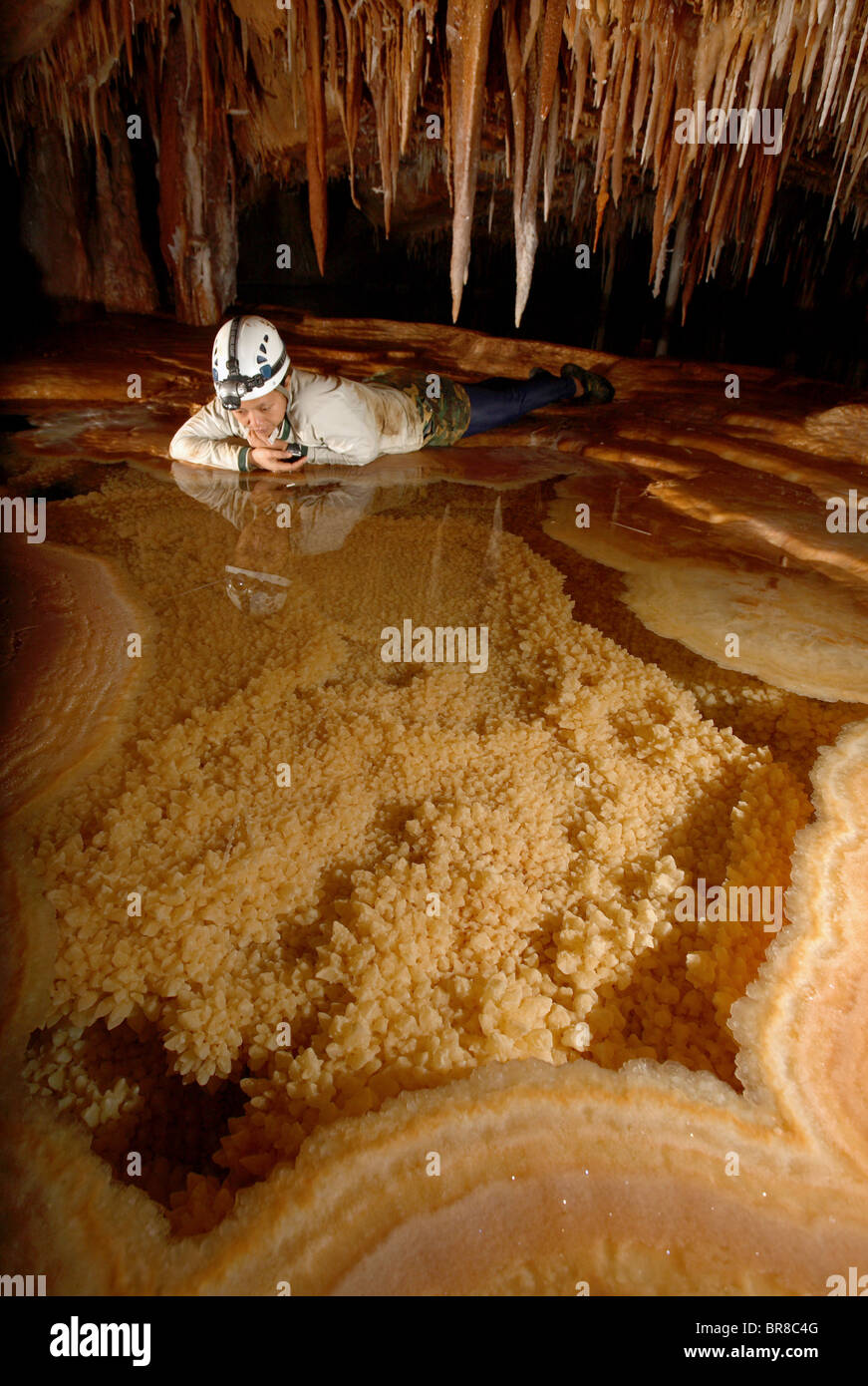 A female cave explorer looks into a very pretty Gour Pool. The floor of which is covered with 'dog tooth' - Stock Image