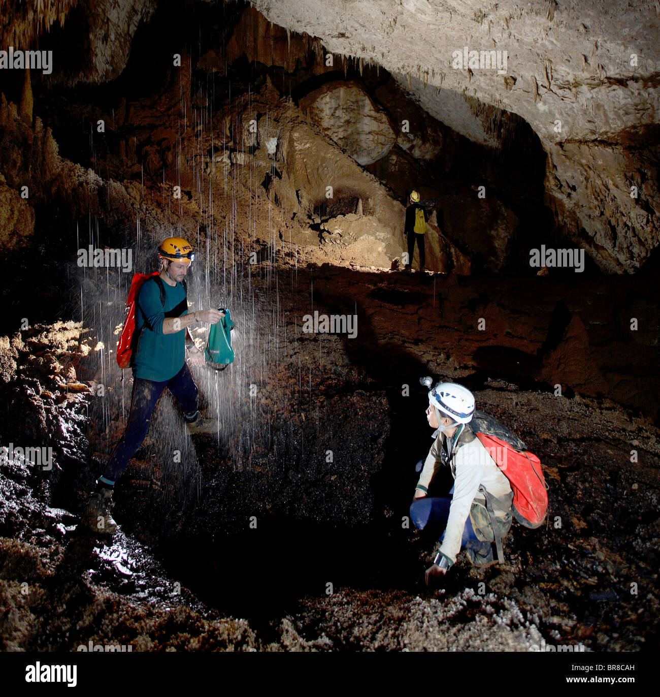 Two cave explorers collect water from an inlet inside Whiterock (cave). When it rained on the surface these inlets - Stock Image