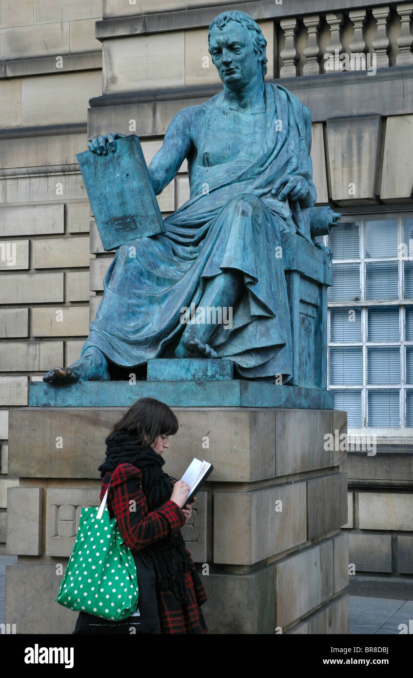 A girl sketches beside the statue of David Hume on the High Street in Edinburgh, Scotland. Stock Photo