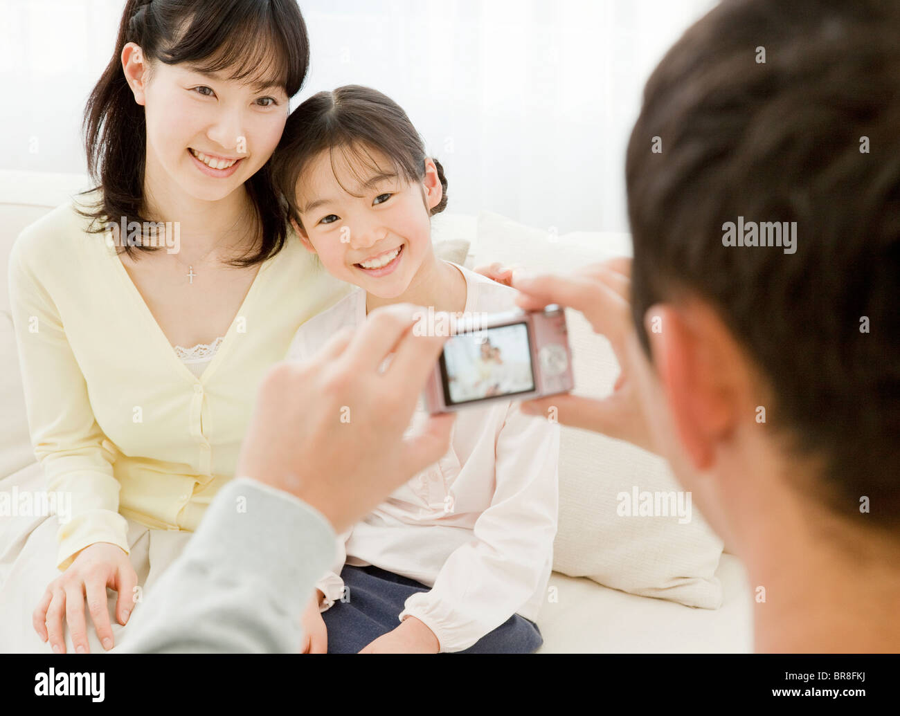 Father taking a photograph of mother and daughter Stock Photo