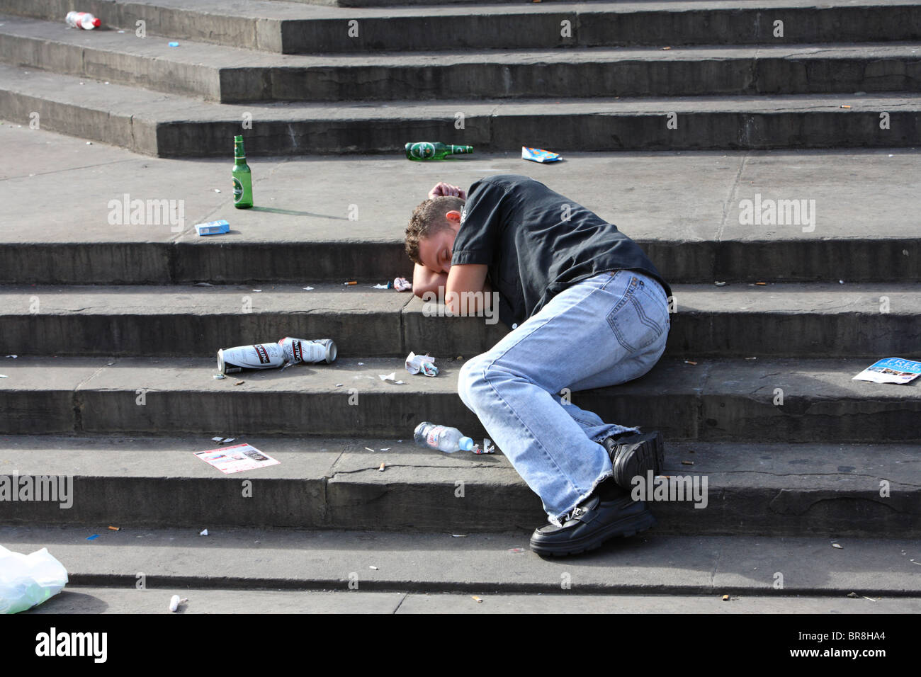 Young man lying asleep on steps of Eros after drinking alchohol, Piccadilly Circus, Westminster, London, W1. - Stock Image