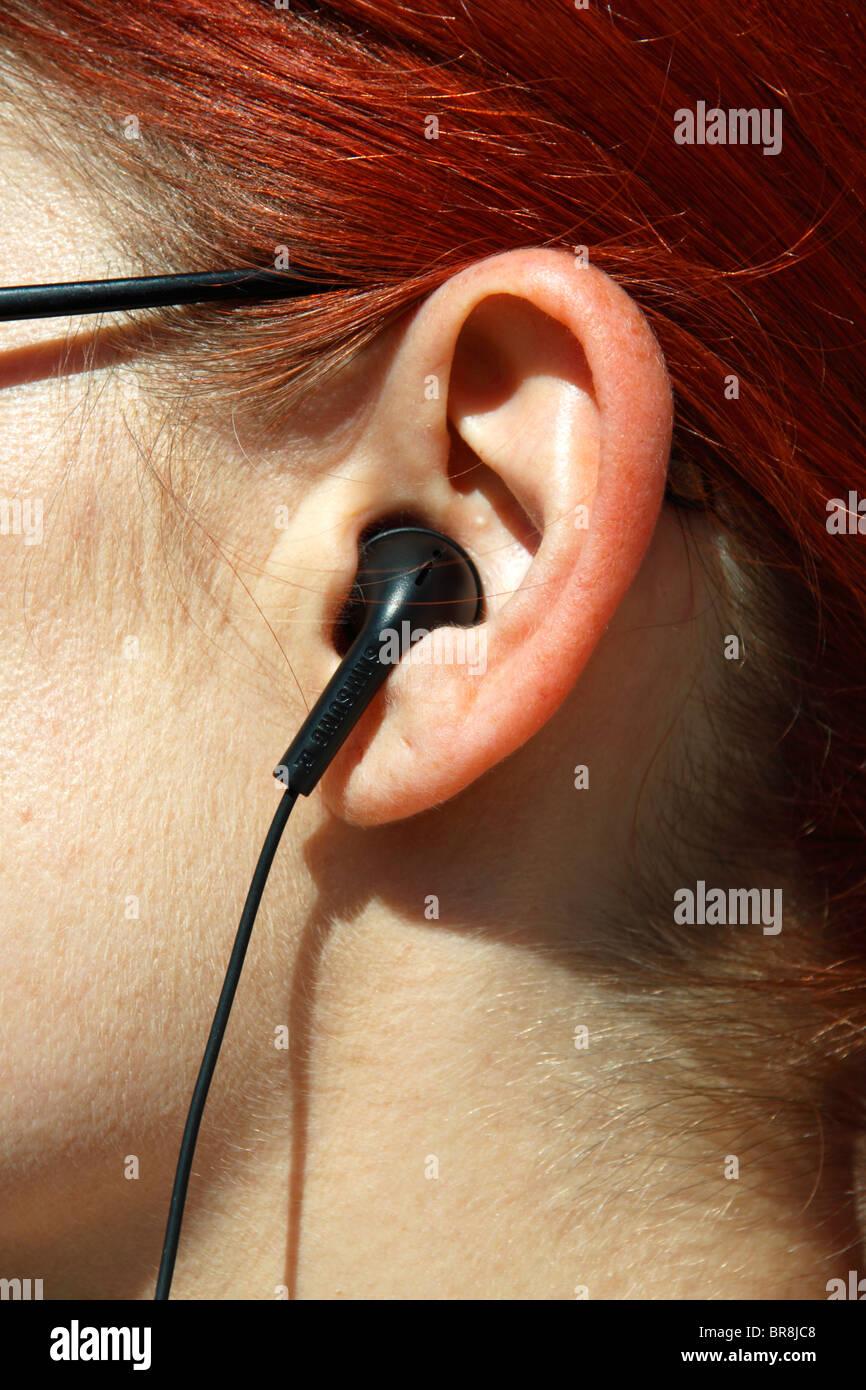 Redheaded woman using earphones. - Stock Image
