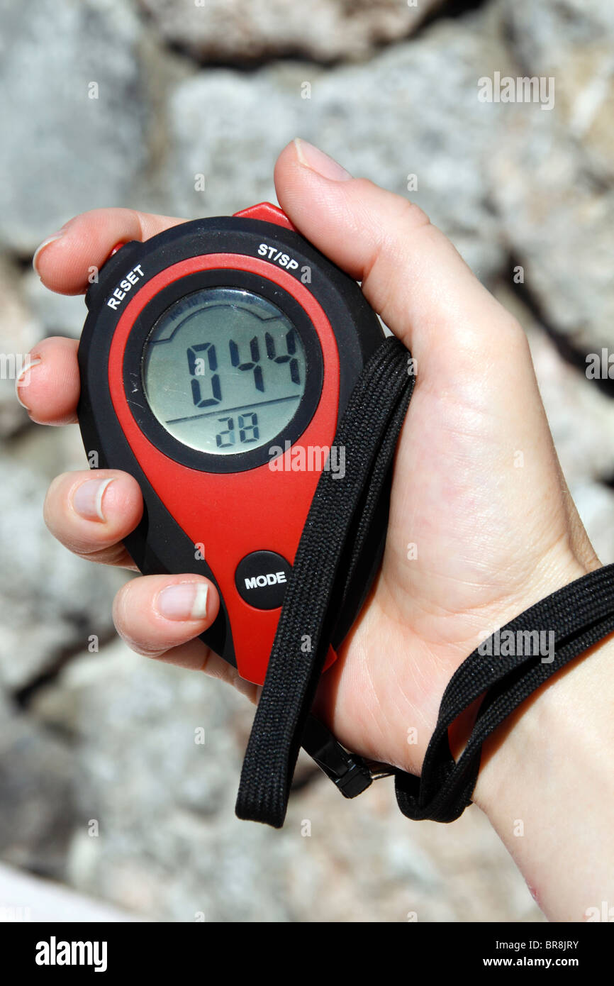 Woman's hand holding a stopwatch - Stock Image