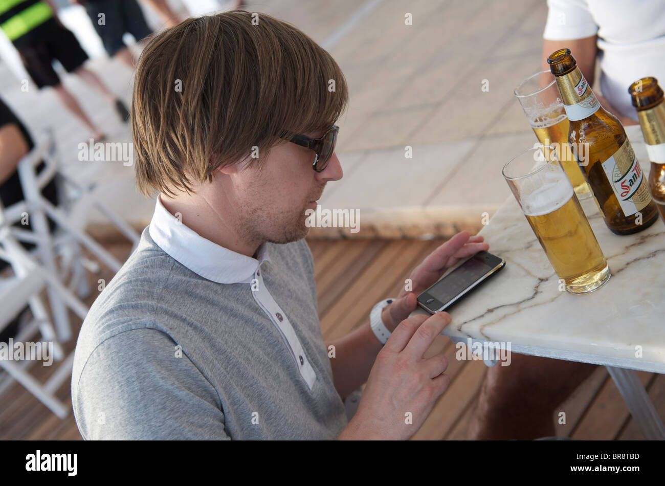 trendy young man using his iphone at cafe del mar, ibiza - Stock Image
