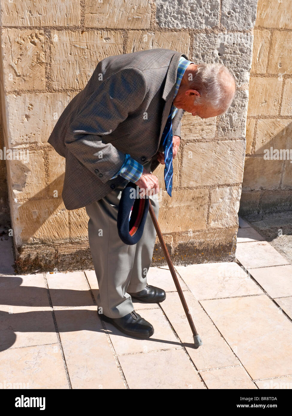 Old hunch-back man with walking stick resting on sidewalk - France. - Stock Image