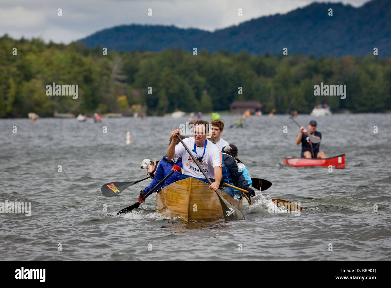 Paddlers with dog cross Fulton Chain of Lakes at Inlet, New York, during Adirondack Canoe Classic, '90-Miler' - Stock Image