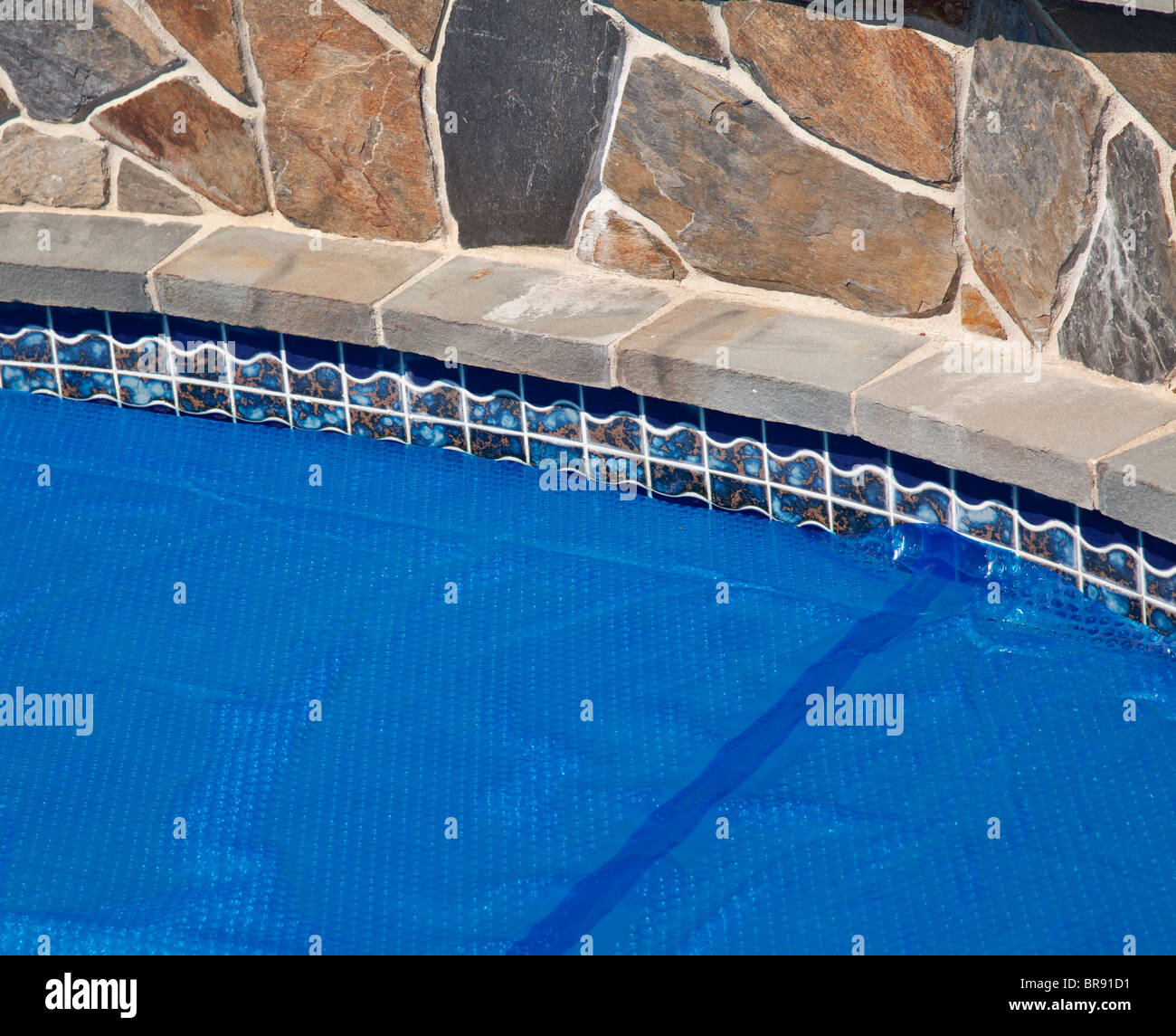Domestic swimming pool with blue solar bubble wrap cover to keep in ...