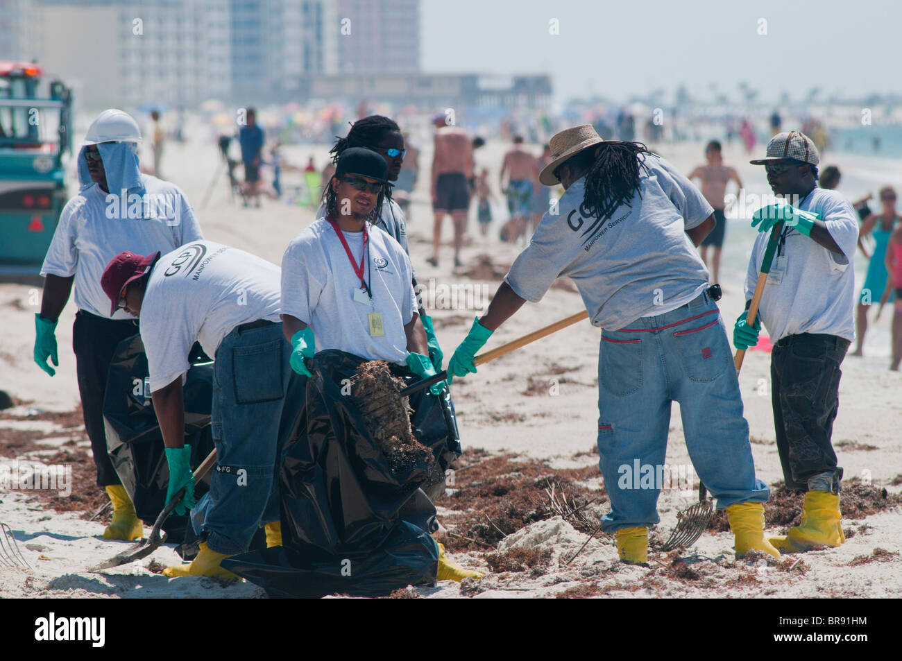 BP crews clean oil from beach, Gulf Shores, Alabama. - Stock Image