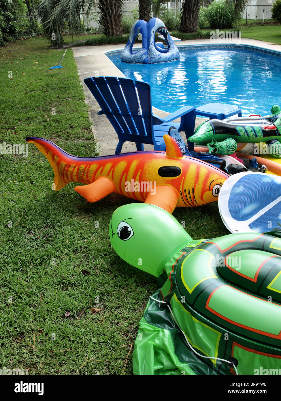 children's pool swimming toys floaters blown-up inflatable sitting beside the edge of a garden backyard with croc Stock Photo