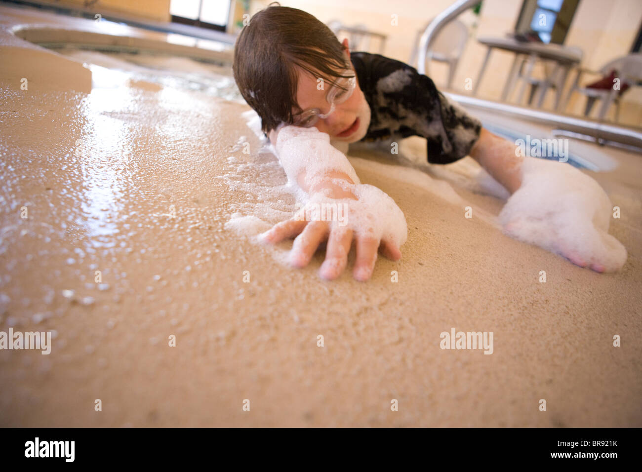 Tired child crawling out of a hot tub covered in foamy bubbles - Stock Image