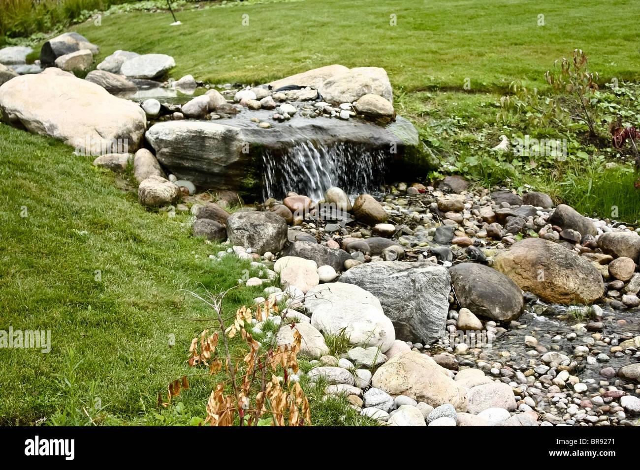 rock running water grass - Stock Image