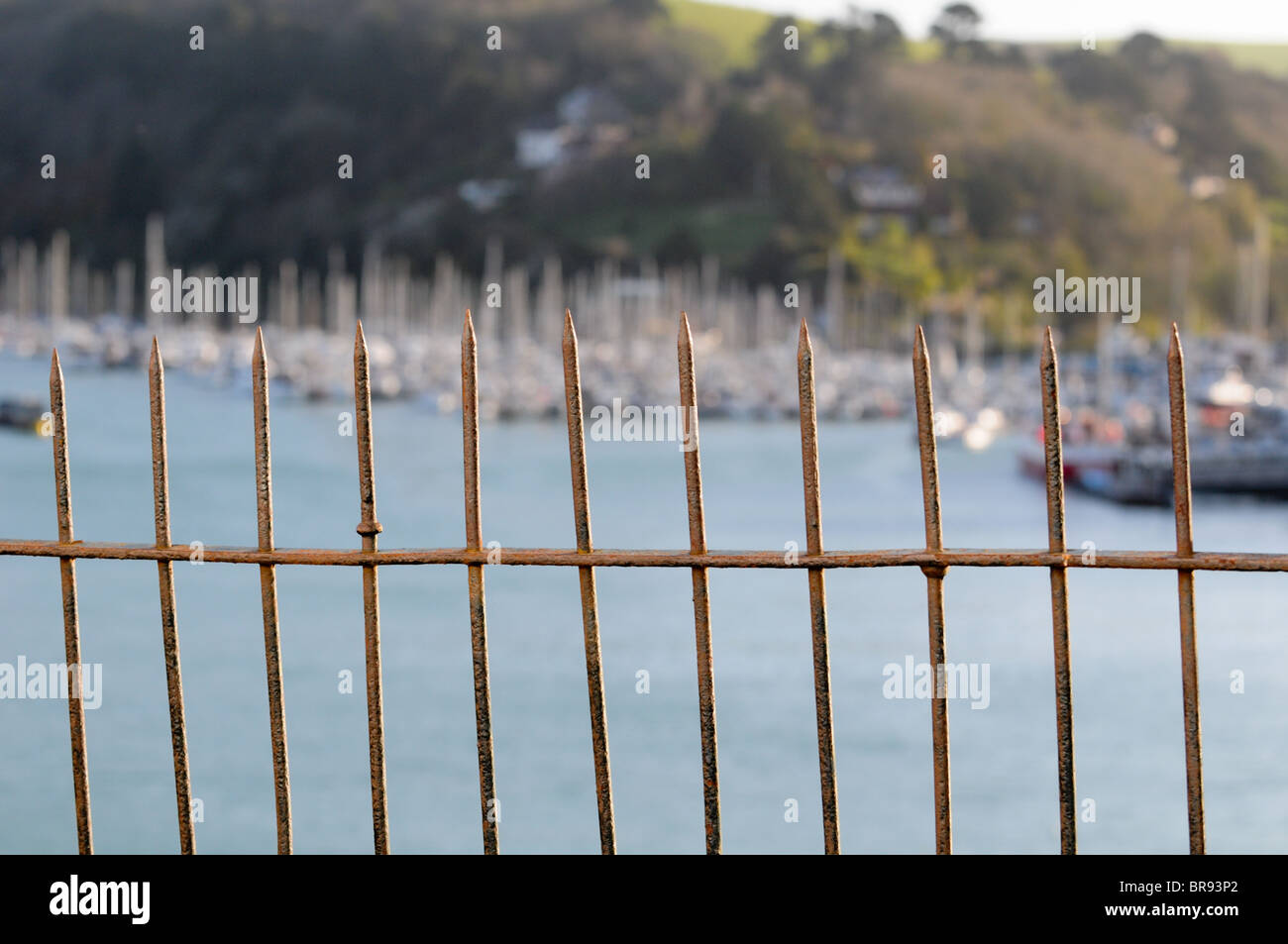 Old thin rusting cast-iron railings on a Dartmouth street with boat masts in Kingswear on the River Dart in the - Stock Image
