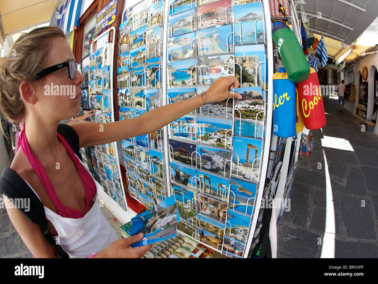 Female Tourist Buying Classic Greek Postcards For Sale  In Lindos Rhodes Greek Islands Greece Hellas - Stock Image