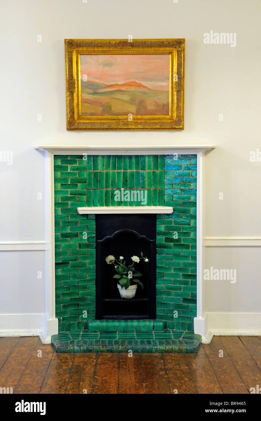 Green tiled fireplace Mary Ward House London England UK - Stock Image