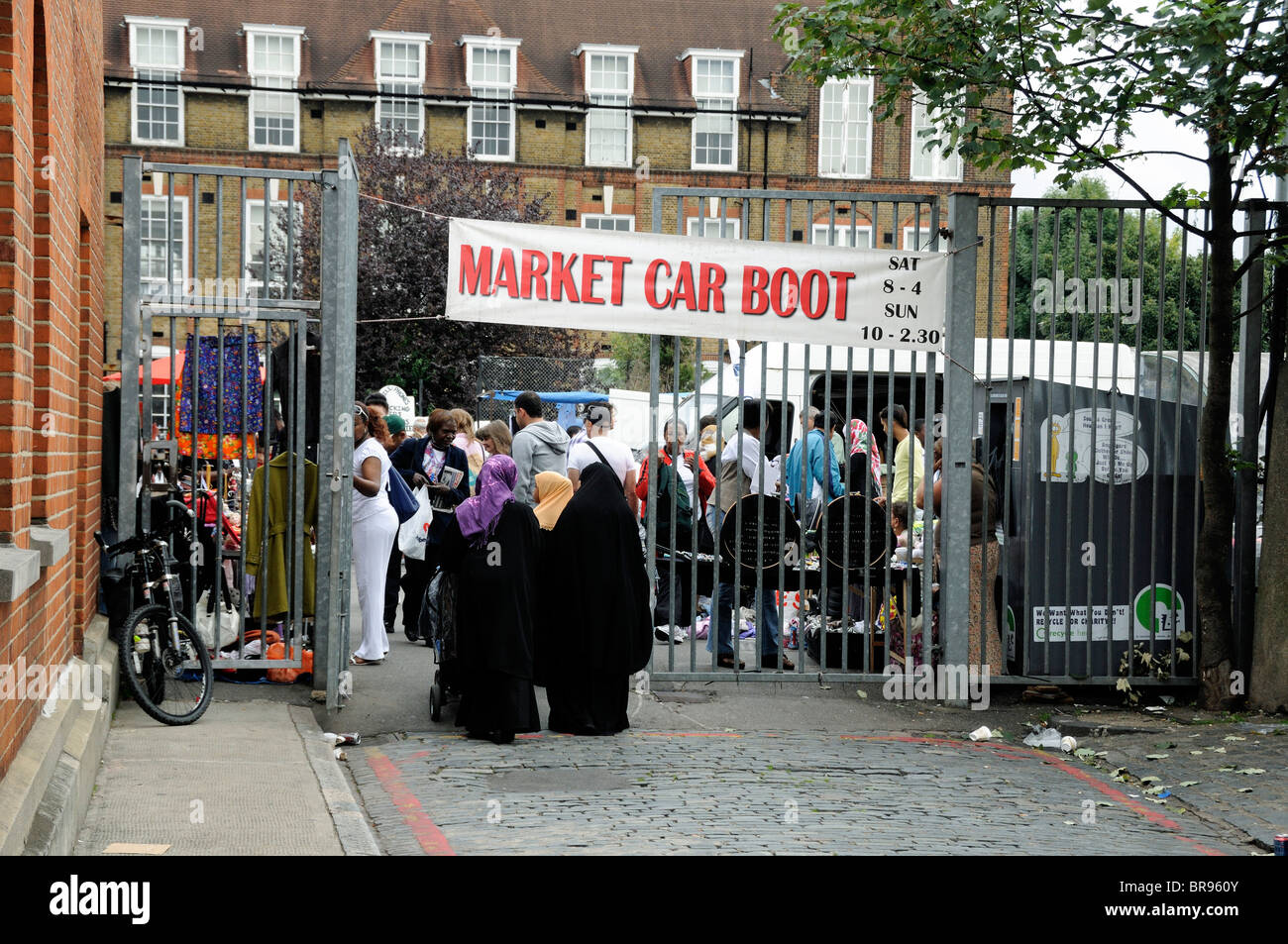 Three ladies entering the gates of a car boot sale Holloway London England UK - Stock Image