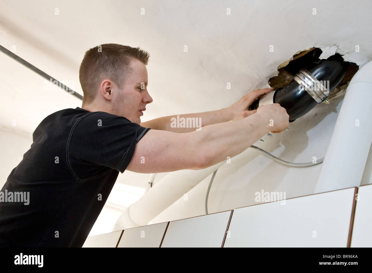 A plumber repairing the leaky drainpipe and water seal - Stock Image