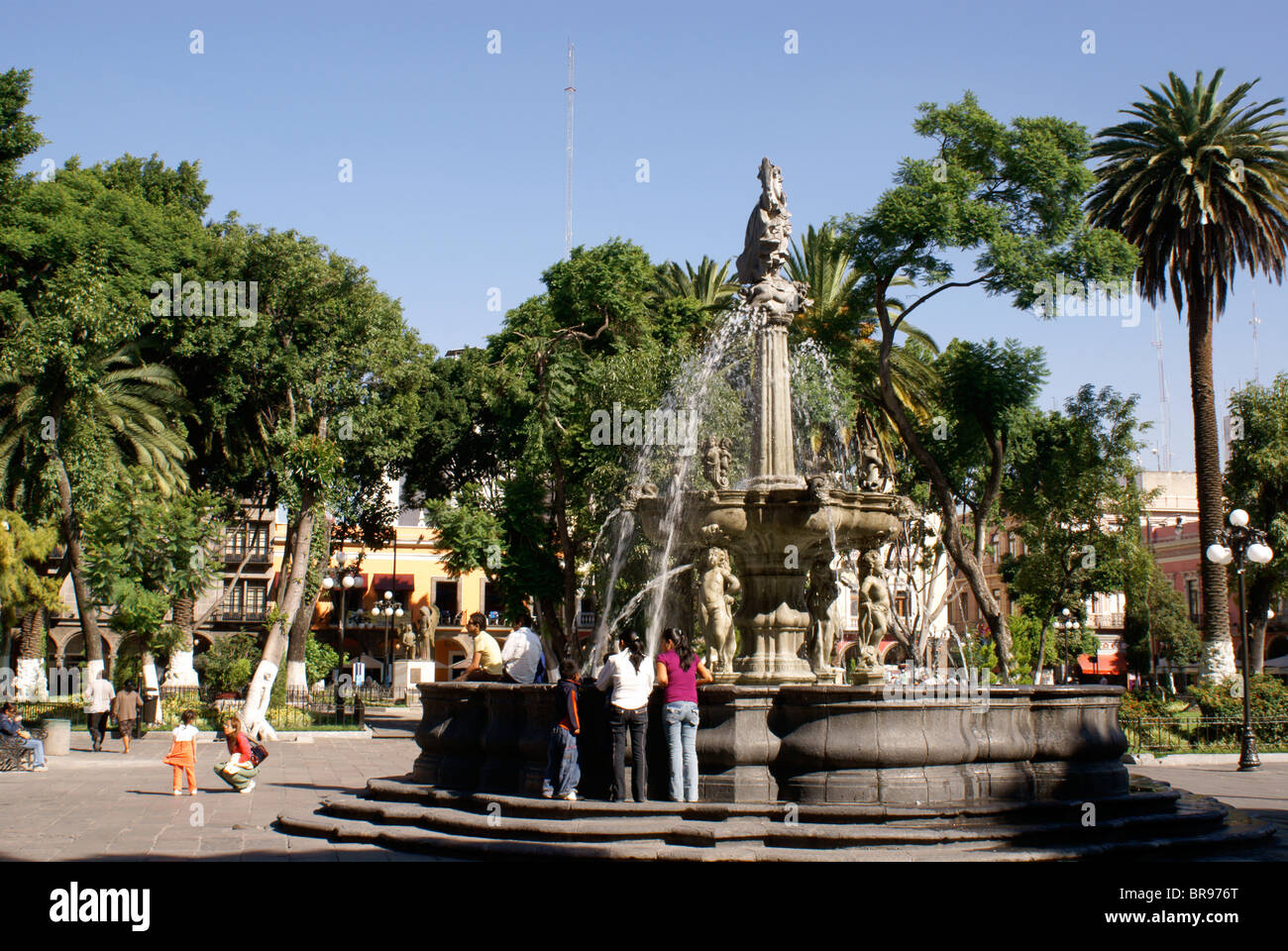 Fountain and people in the zocalo, city of Puebla, Mexico. The historical center of Puebla is a UNESCO World Heritage - Stock Image