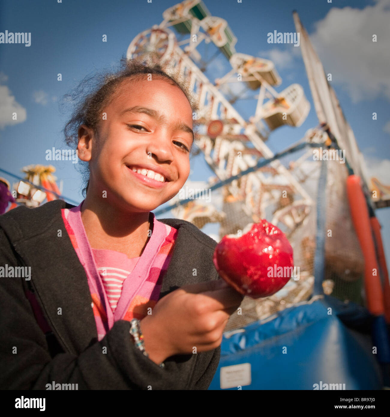 girl eats a candied apple at a state/county fair Stock Photo