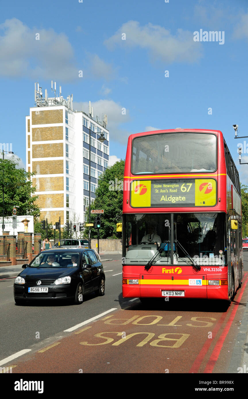Red double decker London bus in bus lane Hackney England UK - Stock Image