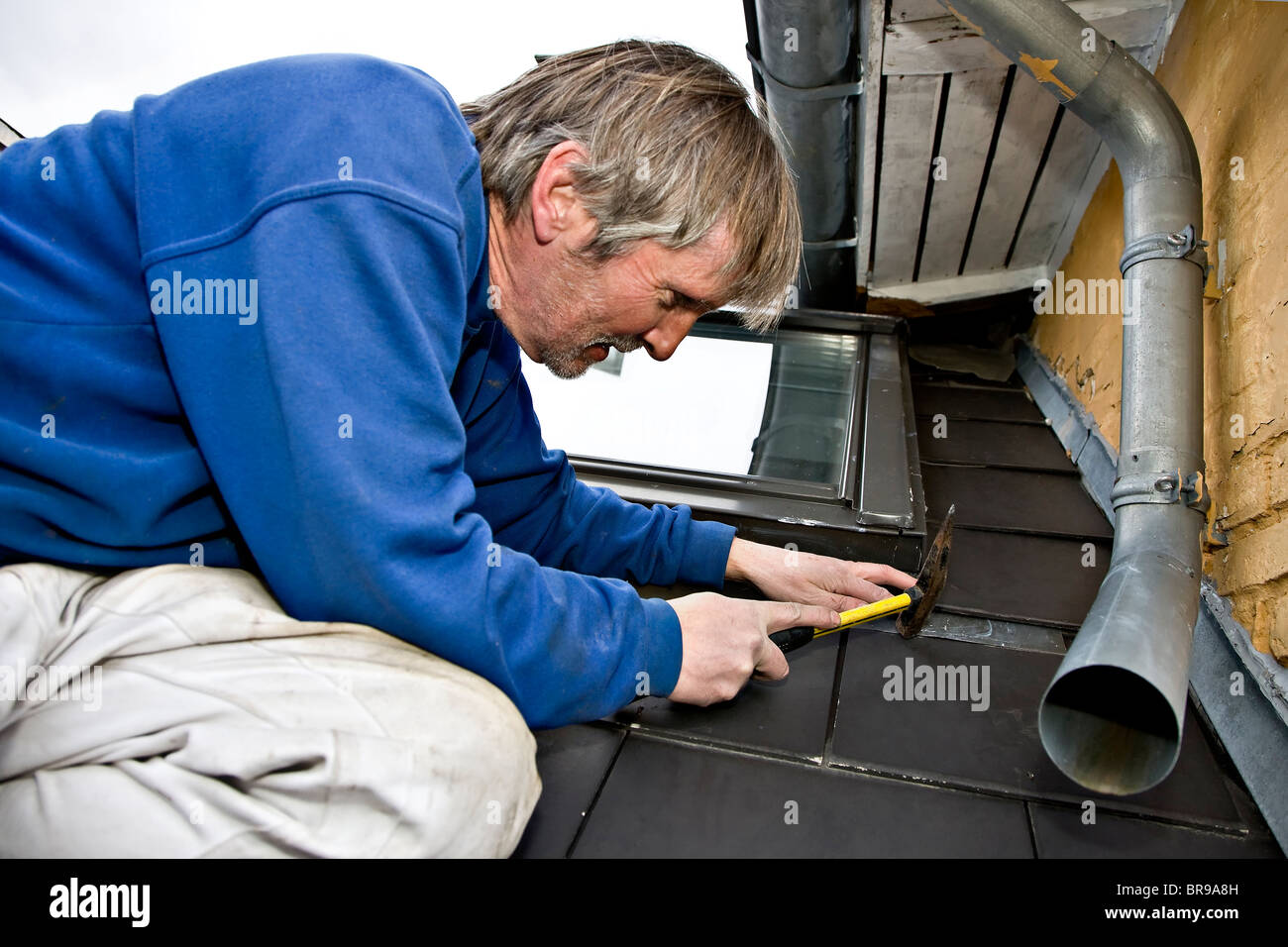 A plumber repairing the leaky roof and drainpipe - Stock Image