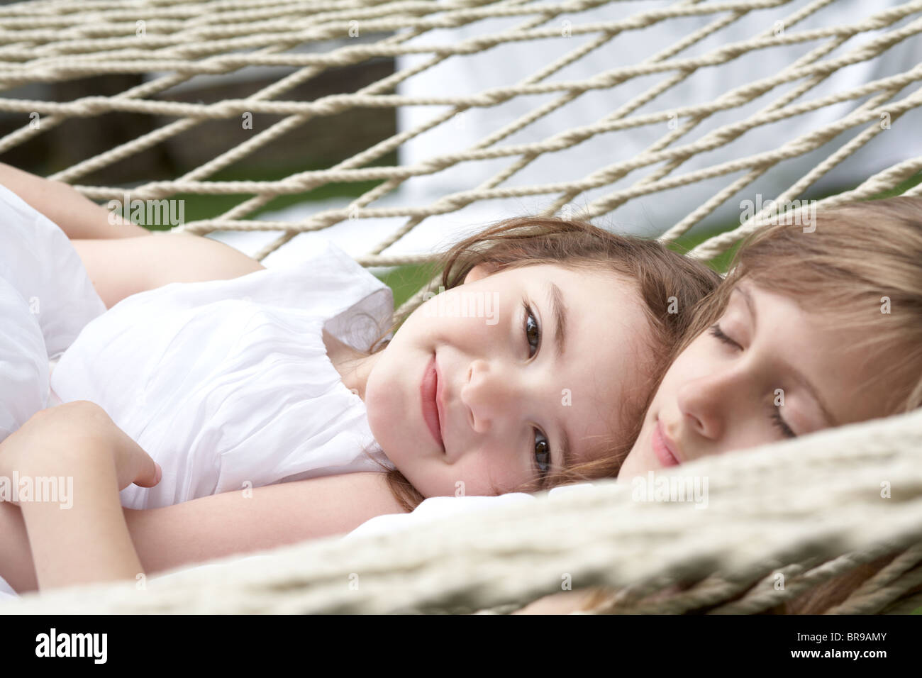 sisters resting in a hammock - Stock Image