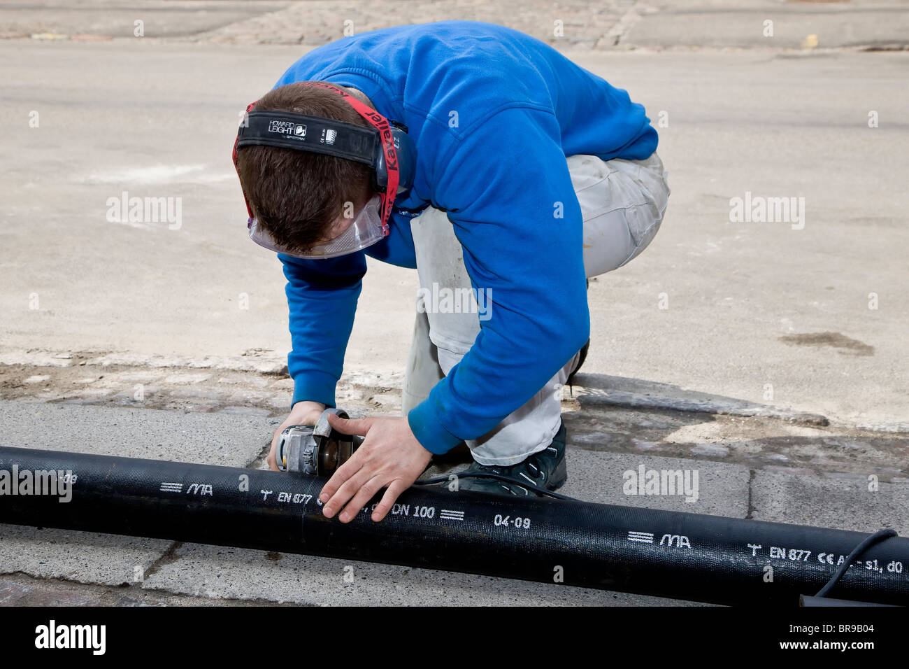 A plumber cutting a new drainpipe with an angle grinder - Stock Image