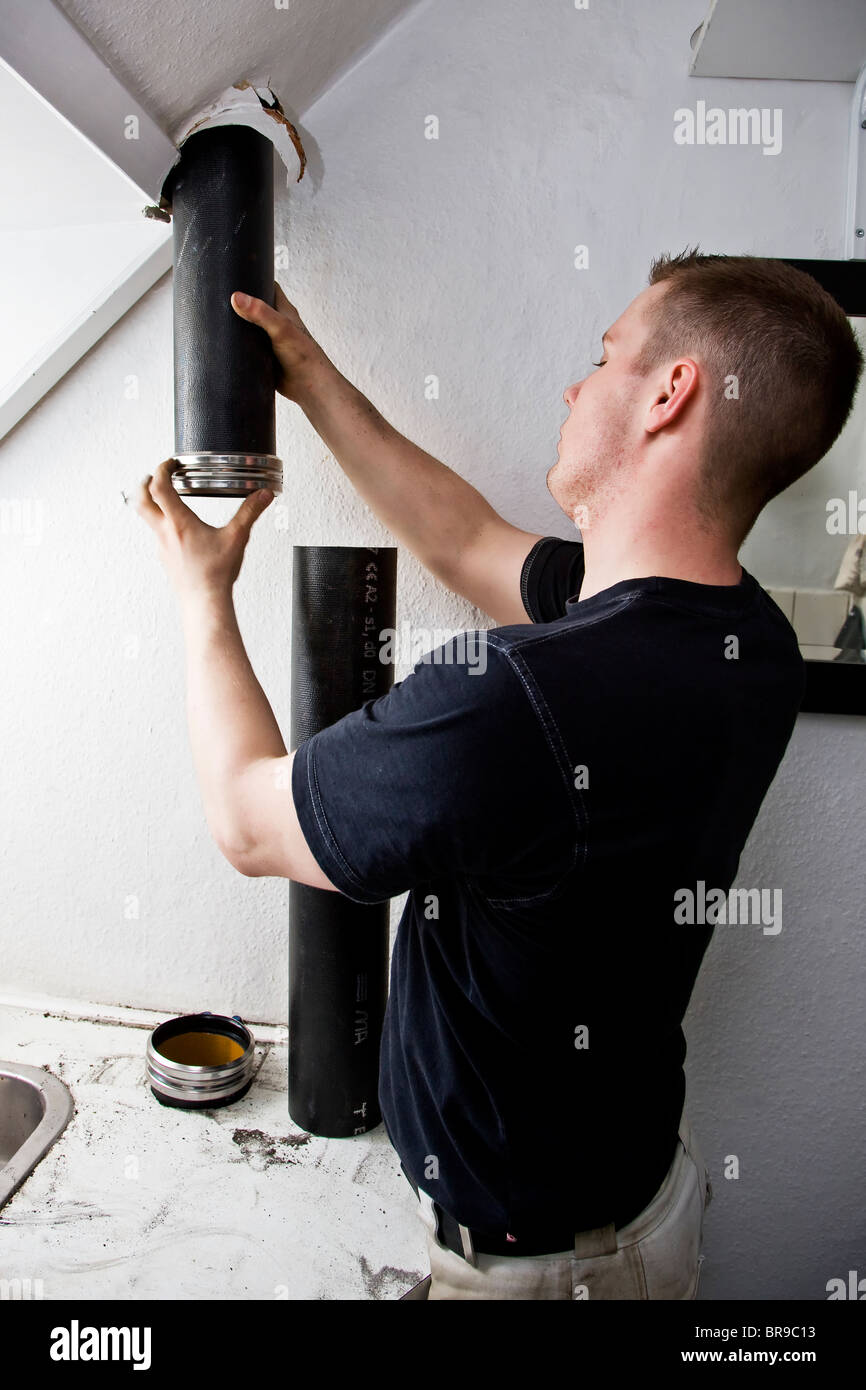 A plumber replace old leaky drainpipe with new pipe - Stock Image