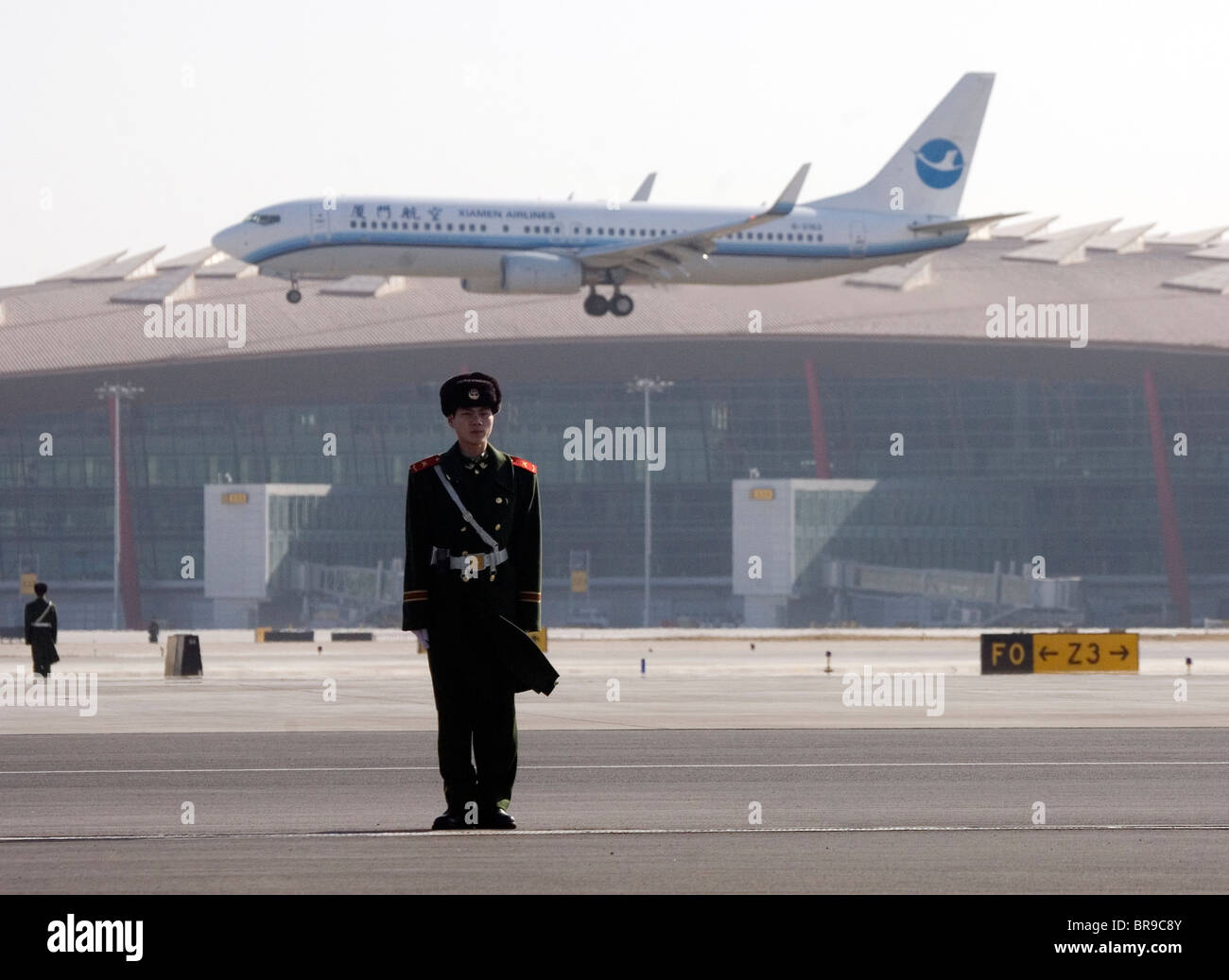 Soldier on tarmac in front of a landing plane at Beijing's new airport China. - Stock Image