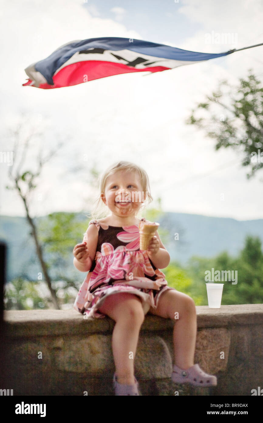 a little girl laughs while eating ice cream in New York State - Stock Image