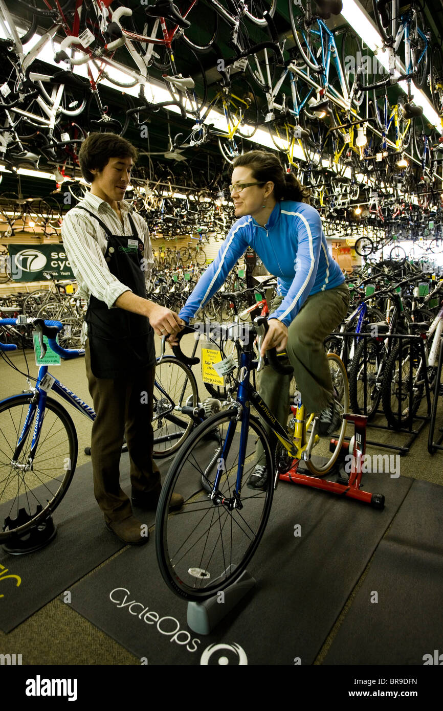 An employee of a bike shop helps a woman test ride a new bicycle Seattle Washington. Stock Photo