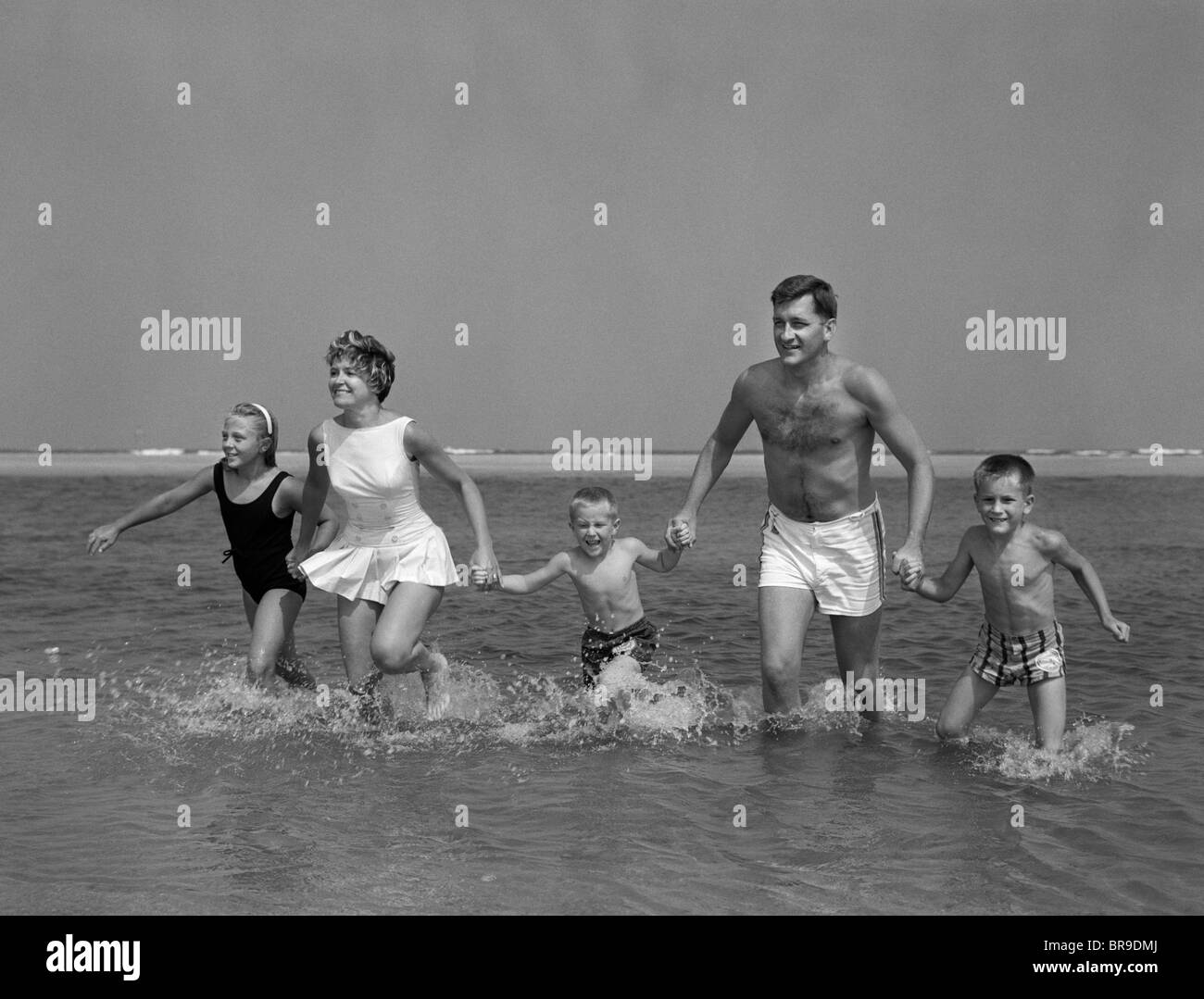 1960s FAMILY HOLDING HANDS RUNNING IN WATER AT OCEAN BEACH - Stock Image